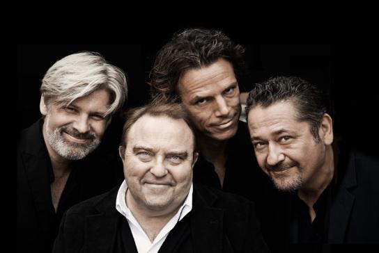 Bild: Vier Männer stehen nah zusammen und lächeln in die Kamera.