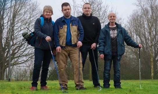 Bild: Vier Personen stehen mit Golf-Ausrüstung auf einem grünen Rasen.
