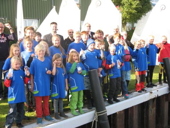 Kinder in blauen T-Shirts im Gruppenbild, im Hintergrund die aufgeriggten Segel der neuen Optimisten auf dem Gelände des OMS