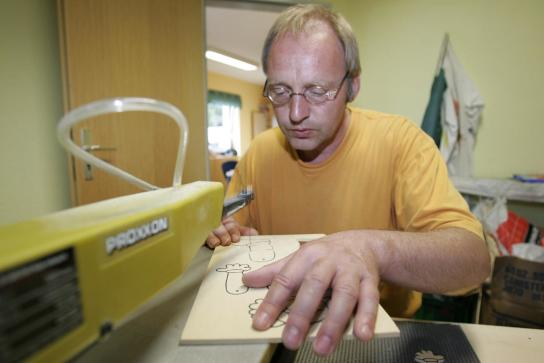 ein Mitarbeiter sägt Holzteile für einen Hampelmann an der Dekupiersäge aus