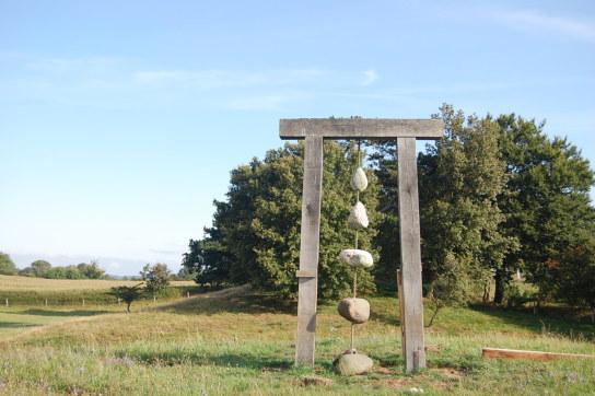 Sie sehen ein Tor aus Holz in dem Steine befestigt sind. Das ganze steht auf einem Hügel.