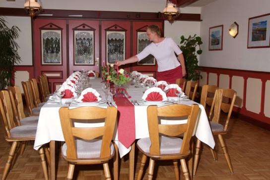 Eine Kellnerin zündet die Kerzen auf einer festlich gedeckten Tafel an.