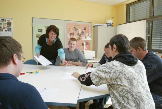 Eine fachkraft zur Arbeits- und Berufsförderung verteilt Arbeitspapiere an die Gruppe