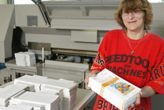 Eine Mitarbeiterin zeigt die fertigen Druckerzeugnisse