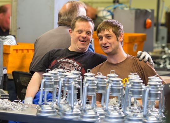 In der Laternenproduktion: zwei männliche Beschäftigte sitzen nebeneinander vor einem Tisch auf dem halbfertige Laternen stehen. Der linke hält den rechten im Arm.