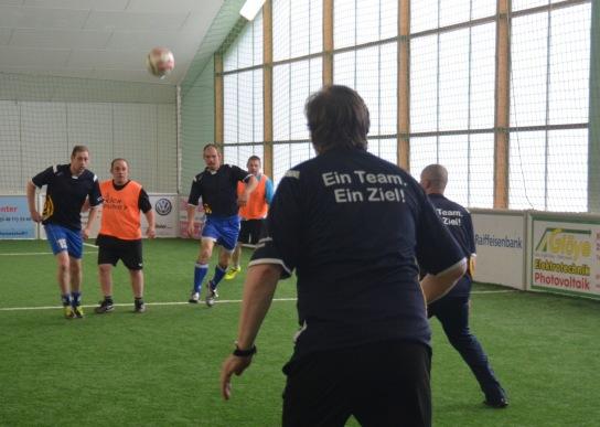 Ein Abwehr-Spieler der Hohenwestedter Werkstatt ist von hinten zu sehen. Er hält seine Position gegen vier Spieler, die den Ball an ihm vorbeispielen möchten.