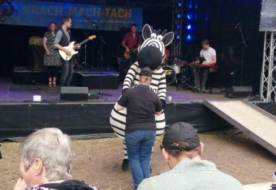 Ein Beschäftigter der Hohenwestedter Werkstatt tanzt ausgelassen mit dem THW-Maskottchen Hein Daddel. Hein Daddel ist ein pummeliges Zebra.