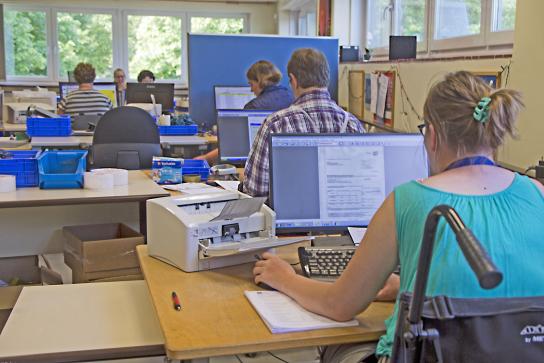 Bild Eine Mitarbeiterin mit Handicap scannt am PC
