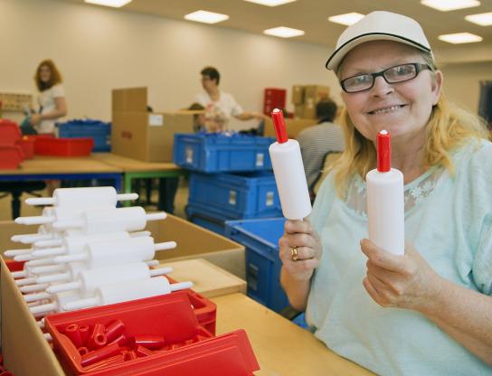 Bild Eine Mitarbeitende mit Handicap präsentiert ein Kinderspielzeug