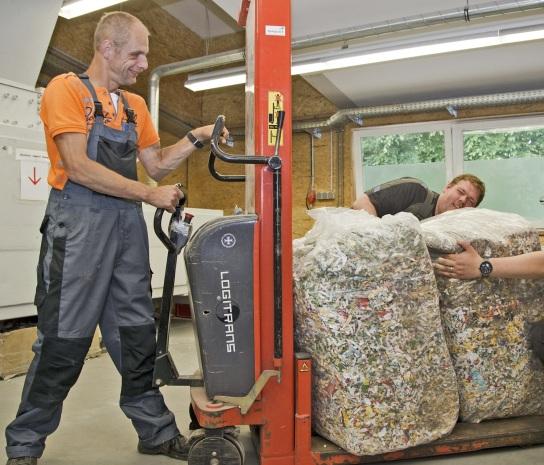 Bild Ein Mitarbeitender mit Handicap transportiert