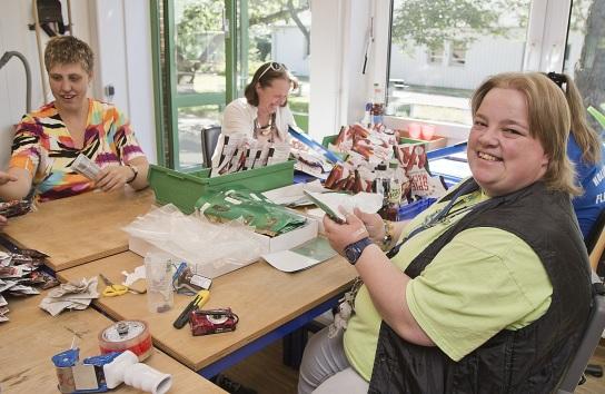 Bild Mitarbeiterinnen mit Handicap sitzen am Tisch