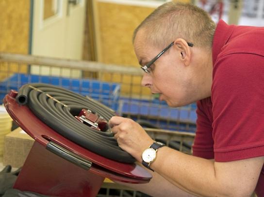 Bild Ein Mitarbeiter mit Handicap rollt Schläuche