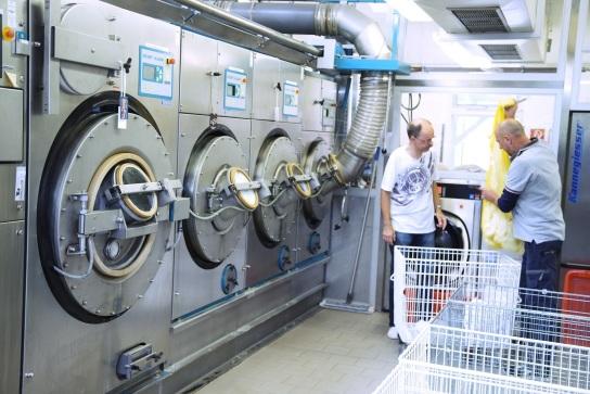 Bild Zwei Mitarbeiter befüllen die Waschmaschinen