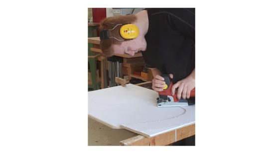 Ein Teilnehmer der Berufsvorbereitung sägt mit der Stichsäge die aufgeklebten Buchstaben aus.