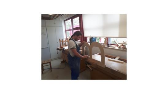 Ein Teilnehmer der Berufsvorbereitung führt Schleifarbeiten am ausgesägten Buchstaben durch.