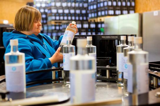 Sabrina kontrolliert die abgefüllten gut2-Flaschen auf Mängel.
