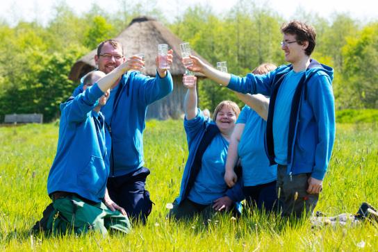 Das gut2-Team stößt mit frischem Quellwasser an. Sie knien im Gras und heben die Gläser. Im Hintergrund sieht man das gut2-Quellhaus.