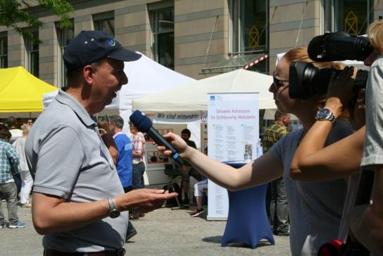 Auch das öffentliche Interesse an der Veranstaltung war groß. Das Programm wurde live beim offenen Kanal übertragen und auch der NDR war vor Ort. Hier Organisator Friedrich Rabe im Gespräch mit der TV-Journalistin.