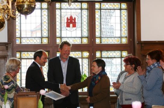 """Bürgermeister Gilgenast überreichte Café-Leiterin Sandra Christmann stellvertretend für ihr gesamtes Team die Urkunde und Plakette """"Auszeichnung zur Barrierefreiheit"""" der Stadt Rendsburg."""
