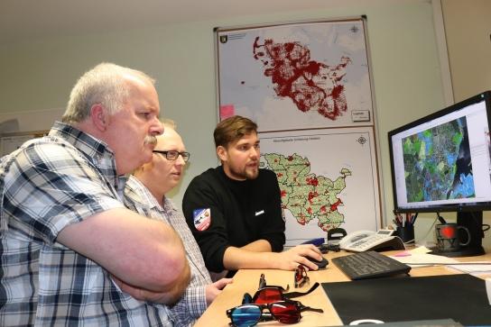 Kai Jensen (3.v.l.) zeigte den Projektmitarbeitern Manfred Schulz  (l., Werkstätten Materialhof) und Bernd Fischer (m., Rendsburger Werkstätten)  wie die Spezialisten vom Kampfmittelräumdienst die eingescannten Bilder nutzen.