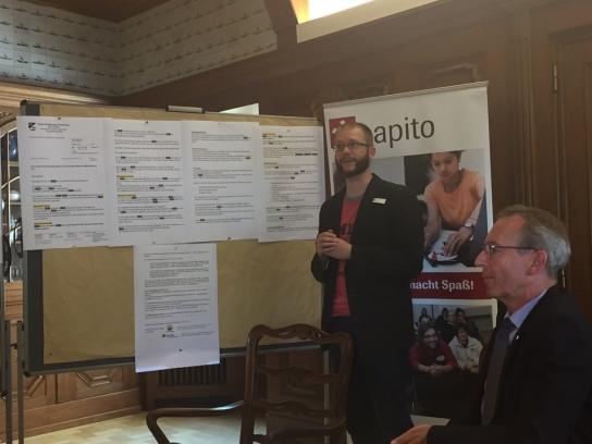 Bild: Ein Mann steht vor einer Pinnwand und deutet auf beschriebenes Papier.