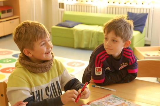 Zwei Jungen an einem Tisch mit Ausmalbuch und Stiften