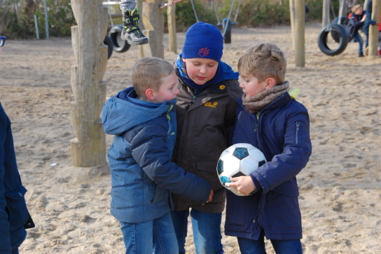 Drei Jungen mit Fußball unterhalten sich auf einem Spielplatz