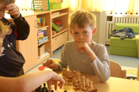 Ein Junge an einem Tisch spielt Schach