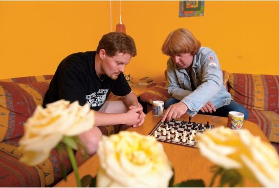 Zwei Männer sitzen auf der Couch und spielen eine Partie Schach in unserer WG Dat Brückenhus, Kiel