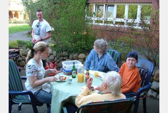 Bewohner und Mitarbeiter beim Grillen im Garten.