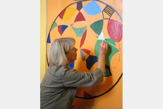 Eine Mitarbeiterin erstellt ein Mandala.