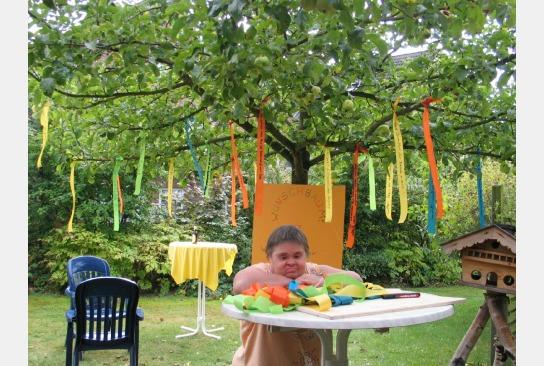 Der festlich dekorierte Garten des Hauses Bickbüschen mit einer Bewohnerin hinter einem Stehtisch.