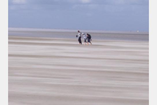 Drei Personen gehen bei Sturm über den Strand