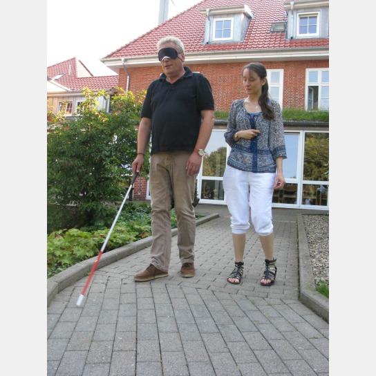 Ein Mann mit Blindenstock und Augenbinde mit einer Frau auf einem Weg