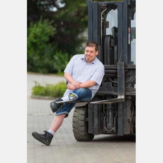 Kai Lehnert, ein Mann mit Behinderung, sitzt nach linksgebeugt auf der Gabel eines Gabelstaplers. Er tragt ein kurzärmeliges, fein, blau-weiß kariertes Hemd und eine kurze Jeanshose. An seinem linken Bein befindet sich eine Schiene.