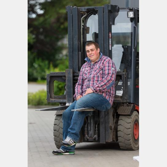 Kim Behrens. Ein Mann sitzt auf der Gabel eines Gabelstaplers. Er trägt ein rot blaues Hemd, eine blaue Jeans und dunkle Schuhe.