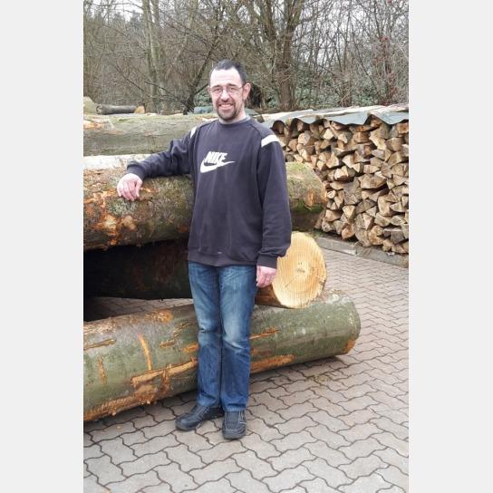 Holger Klay. Ein Mann steht an einem Holzstapel gelehnt. Er trägt einen dunklen Pullover, eine blaue Jeans und dunkle Schuhe.