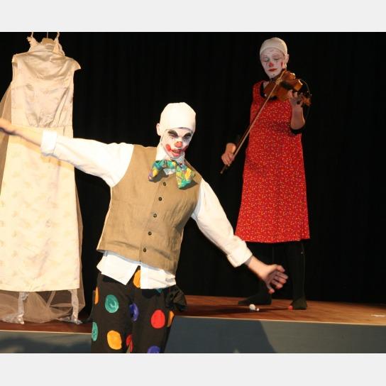 1 Clown beim Kunststück mit Bunter Hose, weißem Hemd, beiger Bluse und grüner Fliege