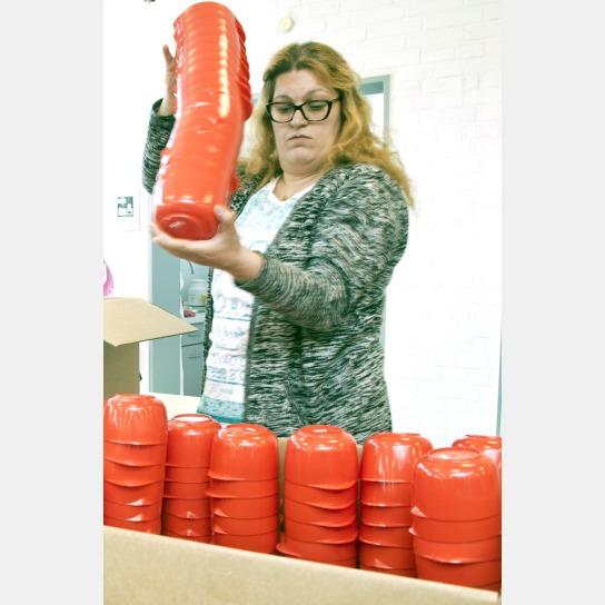 Bild Eine Mitarbeitende mit Handicap stapelt rote