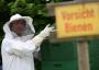 Ein Imker in voller Montur am Bienenstock.