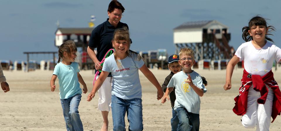 Eine Frau läuft mit fünf Kindern am Strand