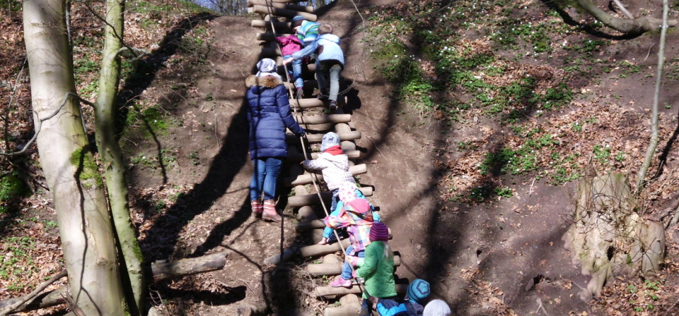 Eine Gruppe von Kindern klettert über eine Holzle