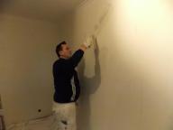 Ein Maler spachtelt eine Wand.