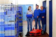 drei Monteure in überwiegend blauer Arbeitskleidu