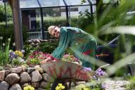 ein Gärtner mit Schiebkarre pflegt ein Blumenbeet