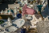 Auf einem Tisch wird schönes altes Geschirr, Lampen, Schüsseln und vieles mehr präsentiert und steht auf dem Flohmarkt zum Verkauf.