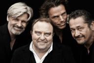 Vier Männer vor schwarzem Hintergrund lächeln in