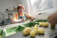 Ein Mitarbeiter schält Kartoffen sauber nach