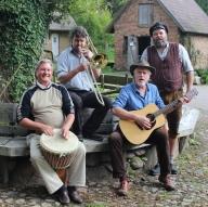 Vier Musiker mit und ohne Instrumente sitzen und stehen vor einer alten Eiche.