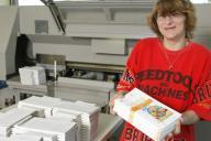 Eine Mitarbeiterin zeigt die fertigen Druckerzeugn